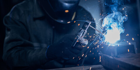 Wall Murals London Professional welder performs work with metal parts in factory, sparks and electricity. Industry worker banner