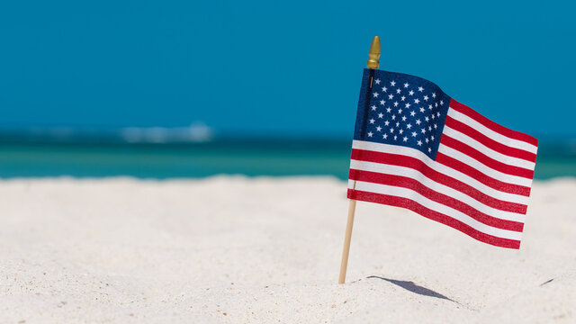 American Flag on the Beach. 4th of July Independence Day. US starry striped patriotic symbol. United States Holidays. Summer vacations. Ocean sand. Bright sunny day and blue color of sea salt water.