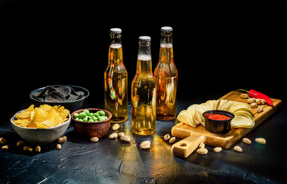 Cold beer with potato chips, snacks and sauce on dark background