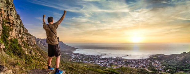 Victory and success after a hike up Table Mountain at sunset. Looking over the bay with a vibrant orange sky - Great outdoors adventure and travel holiday destination, Cape Town, South Africa Wall mural