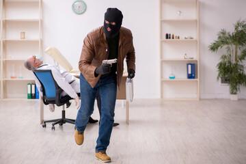 Masked man burglar stealing vaccine from old doctor - fototapety na wymiar