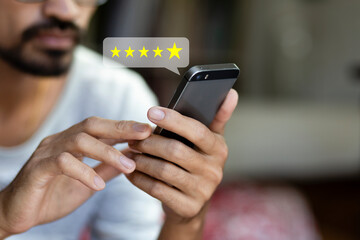 Customer pressing on smartphone with five star icon for feedback review satisfaction service