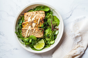 Fried tofu with green salad and nut dressing in white bowl. Asian cuisine, vegan food concept.