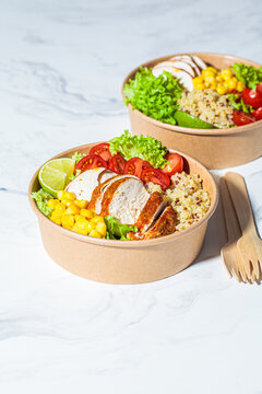Chicken and quinoa salad with corn and tomatoes in craft eco bowl. Zero waste, to go food, recycling packaging, eco friendly concept.