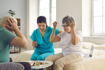 Obraz I win. Happy senior patients playing checkers. Old retired couple and caretaker enjoy intellectual table games. Leisure activities as Alzheimer disease and dementia prevention therapy in nursing home - fototapety do salonu