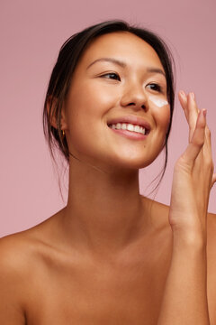 Beautiful South East Asian woman doing her skin care routine