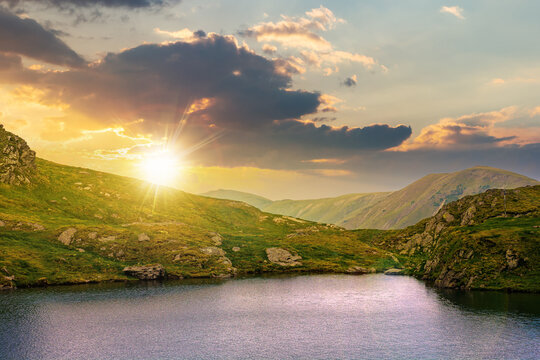 summer landscape with lake on high altitude at sunset. beautiful scenery of fagaras mountain ridge in summer. open view in to the distant peak beneath a fluffy clouds in evening light