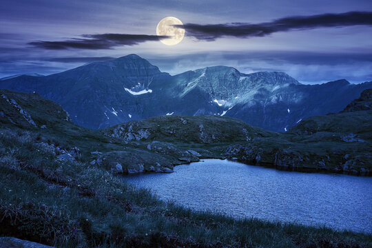 summer scenery with lake on high altitude at night. beautiful landscape of fagaras mountain ridge in summer. open view in to the distant peak beneath a fluffy clouds in full moon light