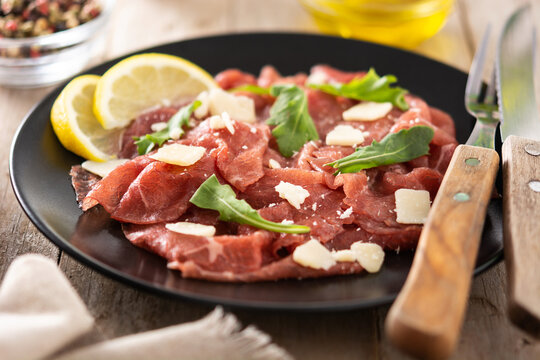 Marbled beef carpaccio on black plate on rustic wooden table