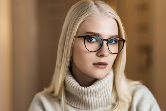 Young stylish woman wearing glasses. Blond business woman looking at the camera
