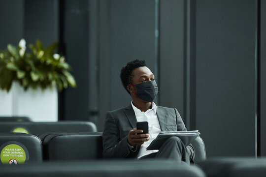 Graphic portrait of African-American businessman wearing mask while working with laptop in waiting lounge at airport with social distancing, copy space
