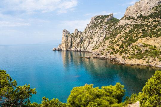 Rocky Crimean coast. Rocks against the background of blue sky and blue sea. Beautiful sunny seascape