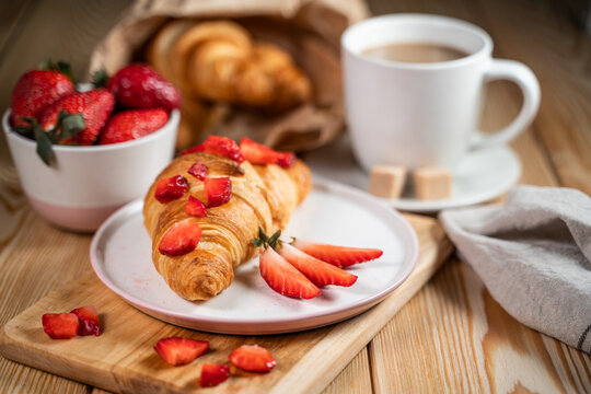 Croissant, fresh strawberries and coffee on a wooden table.