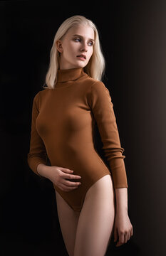 Young blond woman posing on black background. Sexy model in a female bodysuit.