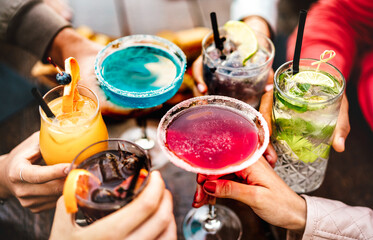 People hands toasting multicolored fancy drinks - Young friends having fun together drinking cocktails at happy hour - Social gathering party time concept on warm vivid filter