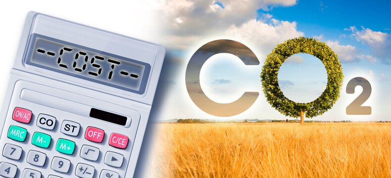 Costs about reduction of the amount of CO2 emissions - concept with CO2 icon text and tree shape in rural scene with calculator