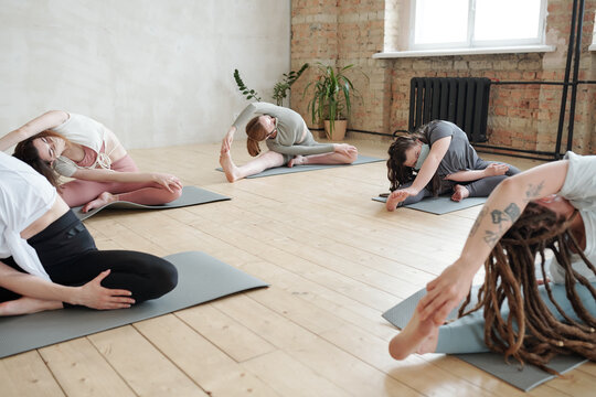 Females in masks doing side-bends on mats while practicing yoga in gym