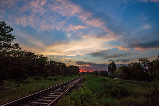Scenic view of railway going straight ahead to sunset with picturesque clouds