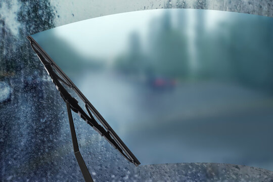 Car windshield wiper cleaning water drops from glass while driving