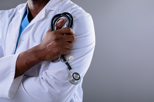 Mid section of african american male doctor holding stethoscope against grey background