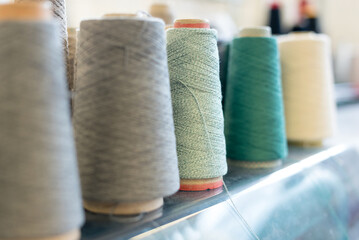 Receding row of cashmere wool on conical spools