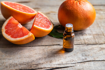 Obraz Grapefruit essential oil in a small bottle. Selective focus. - fototapety do salonu