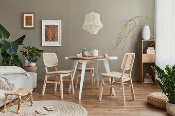 Obraz Stylish interior of dining room with family table, rattan chairs, pendatn lamp, plant, tableware, carpet, decoration and elegant accessories. Template. - fototapety do salonu
