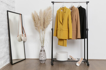 Corner in fashion atelier with fashionable tailored blazers hanging on a rack. Modern premium quality hand made woman's fashion.