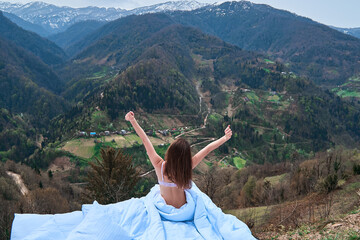 Young woman stretching arms to sky in soft bed while traveling, relaxing outdoor and enjoying silence, tranquility and mountains view