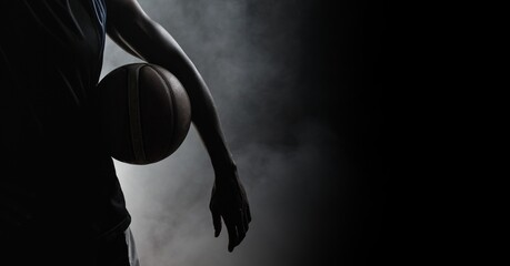 Composition of athletic male basketball player over smoke on black background