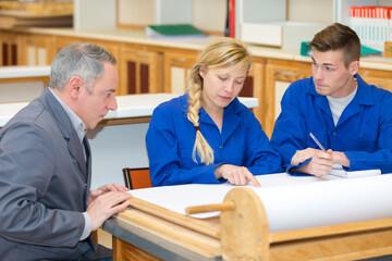 Obraz students wearing blue jackets sat at desk talking to teacher - fototapety do salonu