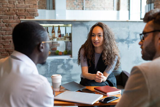 Young businesswoman looking at African partner during discussion of contract terms