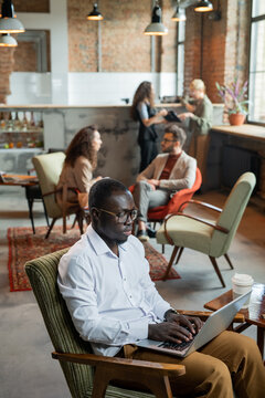 Serious African businessman using laptop against busy colleagues