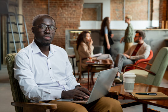 Serious African businessman keeping hands on laptop keypad against interacting colleagues