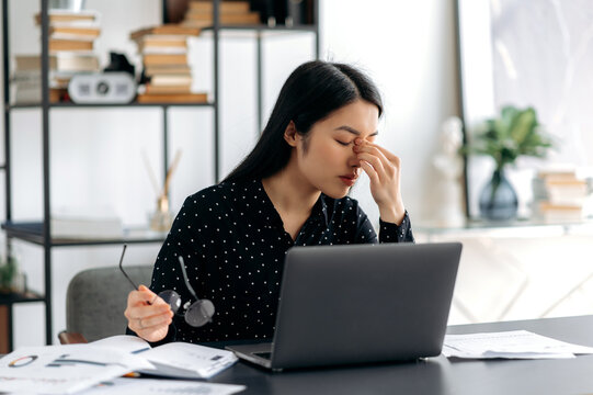 Exhausted asian girl, freelancer or manager, tired of working with laptop while sits at her workplace. Overworked business woman rubs the bridge of her nose, holds glasses in her hand, closes her eyes
