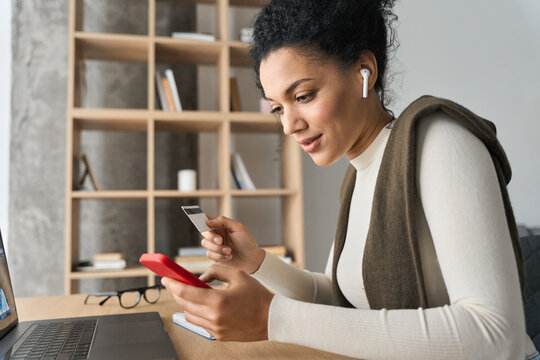 Young adult African American female consumer holding credit card and smartphone sitting at desk at home doing online banking transaction. E commerce virtual shopping, mobile banking concept.