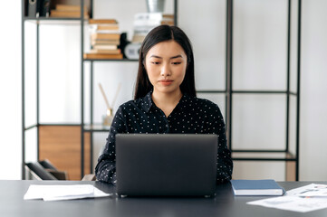 Beautiful successful young asian business woman, manager, CEO, in stylish clothes, sitting in office, using laptop, watching training videos, texting with client or employee, looking at screen