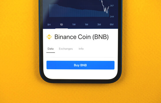 Buy Binance coin BNB cryptocurrency, mobile app with button, concept of online trade and exchange by using smartphone, banking application, top view of business office desk