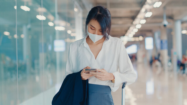 Asian business girl use smart phone for check in boarding pass walk with luggage to terminal at domestic flight at airport. Business commuter covid pandemic, Business travel social distancing concept.