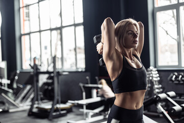 Athletic woman trains triceps with a dumbbell in her hand. French dumbbell press. Healthy lifestyle - fototapety na wymiar