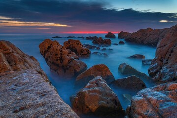 Skały w Oceanie Atlantyckim na tle kolorowego nieba - długie naświetlanie