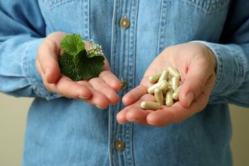 Obraz Woman holds herbal medicine pills, close up - fototapety do salonu