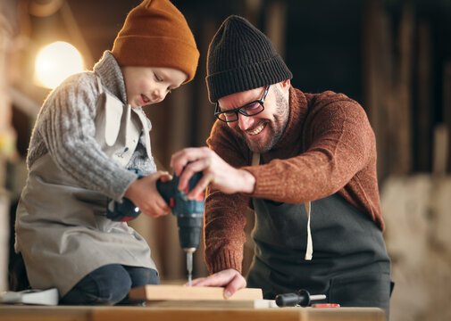 Father and son drilling wooden detail in workshop