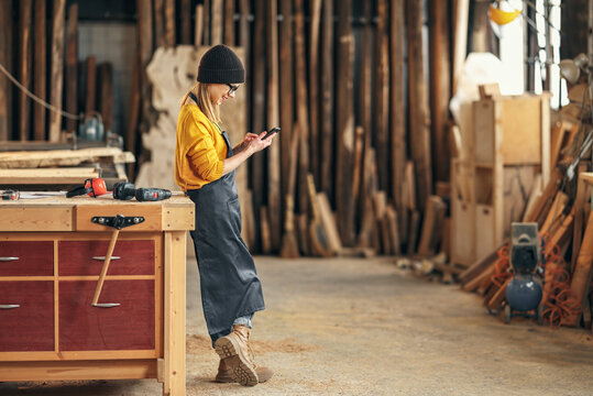 Female joiner using smartphone in workshop