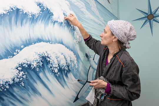 Mature Woman Artist Paints Sea Waves - Mural On A Marine Theme On The Wall