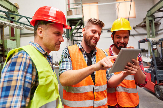 Arbeiter und Lagerist lesen eine Email mit Kundenauftrag