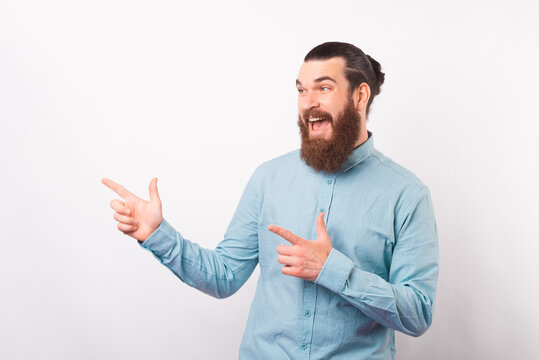 Amazed screaming bearded man in casual pointing away over white wall