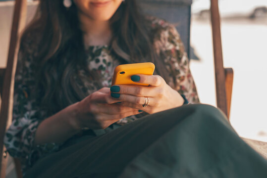 Close up photo of woman sitting outdoor and using smartphone
