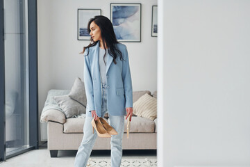 Domestic room. European woman in fashionable stylish clothes is posing indoors