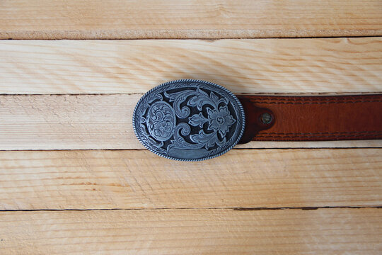 Leather cowboy belt on wooden background